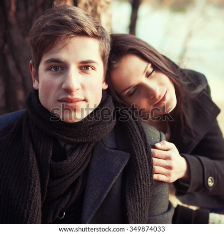 Quiet sensual portrait of pretty young couple in love posing in winter forest  - stock photo
