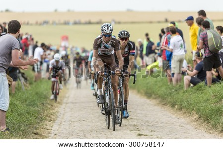 QUIEVY,FRANCE- JUL 07: The peloton riding on a cobblestone road during the stage 4 of Le Tour de France on 07 July,2015 in Quievy, France. - stock photo