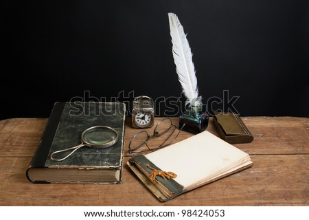 Quill ink pen and inkwell, antique book, magnifying glass, old notepad, vintage clock, spectacles on wood table - stock photo