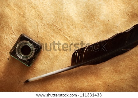 quill pen and inkwell on vintage paper background - stock photo