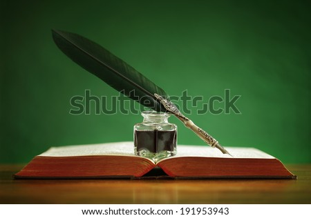 Quill pen and inkwell resting on an old book with green background concept for literature, writing, author and history - stock photo
