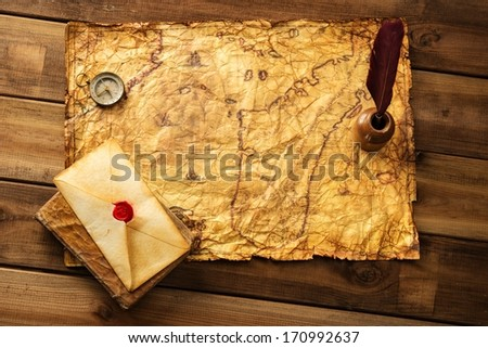Quill pen, compass and envelope on old map over wooden background  - stock photo