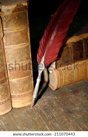 Quill pen on books - stock photo