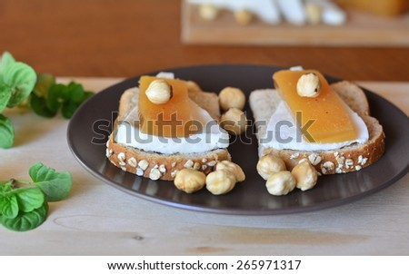 Quince And Fresh White Cheese On Bread Toast On A Brown Plate On The Wooden Table - stock photo