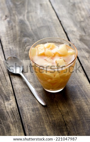 Quince  compote in glass bowl on wooden table - stock photo