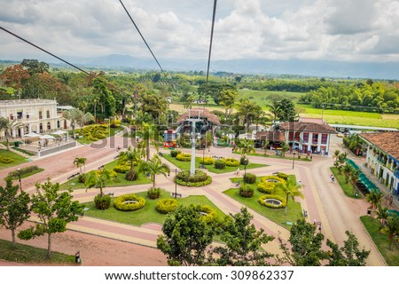 QUINDIO, COLOMBIA - FEBRUARY 23, 2015: NATIONAL COFFEE PARK, COLOMBIA, Downward view of cable car path inside National Coffe Park showing plaza where trip begins shot from passenger point view - stock photo