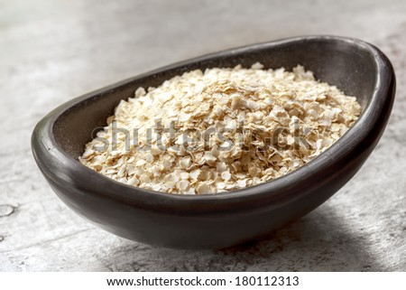 Quinoa flakes in small black bowl over rustic wood. - stock photo