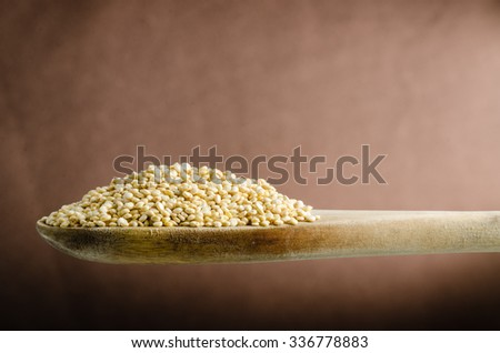 quinoa in a spoon, close up, color background - stock photo