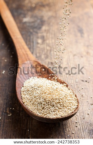 quinoa in a wooden spoon on a background of the dark old wooden table in rustic style - stock photo