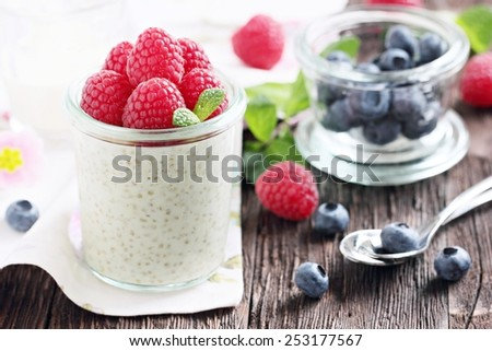 Quinoa porridge ( pudding ) with fresh berries on a rustic wooden table. Selective focus. - stock photo