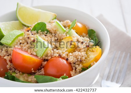 Quinoa salad in bowl, tomatoes and spinach on white wooden table  - stock photo