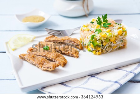 Quinoa salad with deep fried breaded vegan fillet made of tofu - stock photo