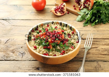 quinoa salad with pomegranate on rustic kitchen table - stock photo