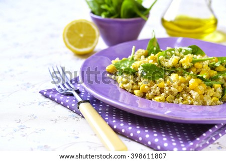 Quinoa salad with spinach and sweet corn on a purple plate.Vintage style. - stock photo