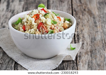 Quinoa salad with vegetables mix, chickpea and cheese. - stock photo