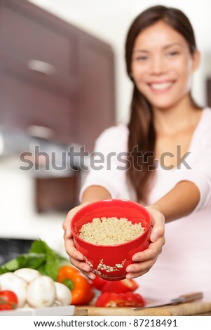 quinoa. Woman showing bowl of cooking quinoa to use for healthy salad. Smiling multiracial female model. - stock photo