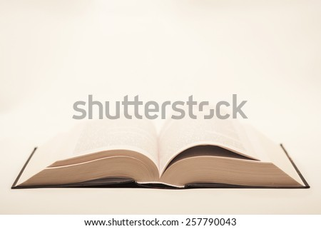 quite old but not damaged open book lying on the table on a light background - stock photo