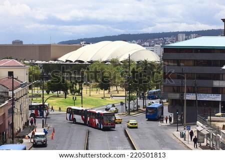 QUITO, ECUADOR - AUGUST 6, 2014: Unidentified people on the Gran Colombia Avenue with the Parque del Arbolito and the Casa de la Cultura Ecuatoriana in the back on August 6, 2014 in Quito, Ecuador  - stock photo