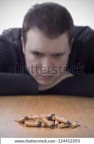 quitting smoking, pile of cigarette butts on table with man looking at it in background - stock photo