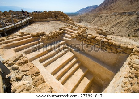 QUMRAN, ISRAEL - OCT 15, 2014: Tourists are visiting the excavations and ruins of Qumran in Israel close to the Dead Sea - stock photo