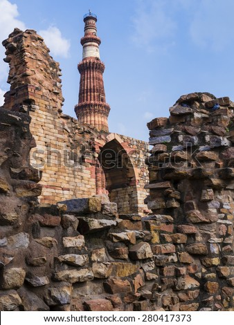 Qutb Minar surrounded by its ruins, Mehrauli archaeological park, Delhi, India  - stock photo
