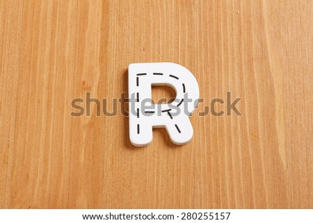 R, spell by woody puzzle letters with woody background - stock photo