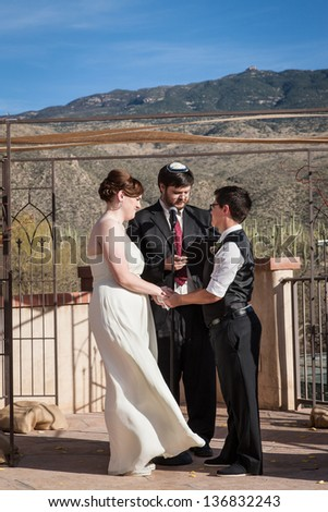 Rabbi reading sacrament for happy lesbian couple marring outdoors - stock photo