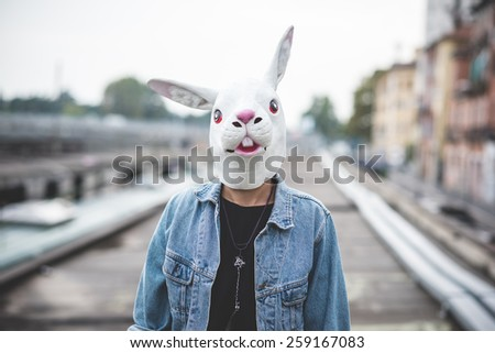 rabbit mask young handsome bearded hipster man in the city - stock photo