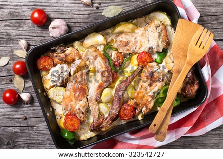 rabbit meat baked in sour cream with tomatoes, peppers, garlic, potatoes and spices,view from above, horizontal. rustic style - stock photo