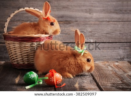 rabbits with Easter eggs on wooden background - stock photo