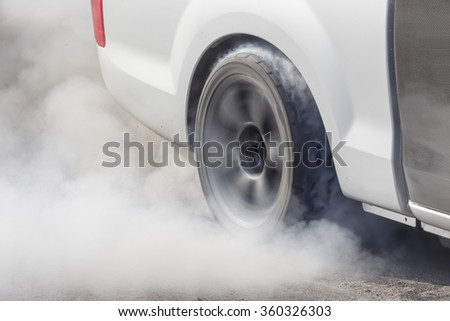 race car burns rubber off its tires in preparation for the race - stock photo