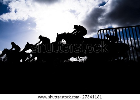 race horse jumping hurdle photographed in silhouette - stock photo