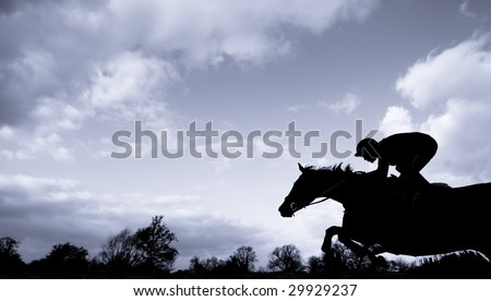 race horse jumping over a hurdle at speed photographed in silhouette with room for titles - stock photo