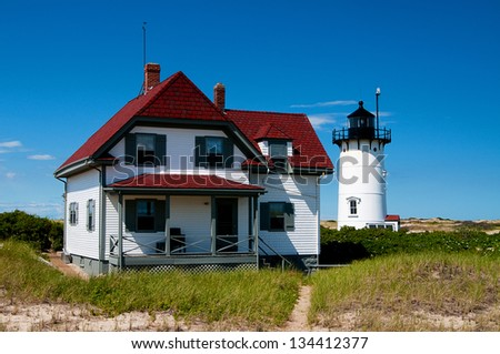 Race Point Lighthouse can be reached from hiking through soft sand. Visitors can also stay at the keeper's quarters and surrounding buildings. - stock photo