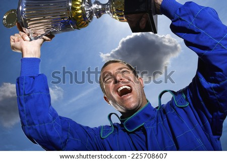 Racecar Driver Holding Trophy - stock photo