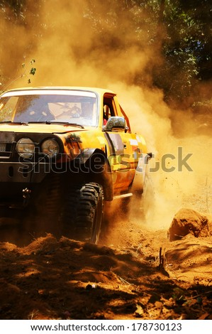 Racer at terrain racing car competition, the car try to cross extreme off road with red earth,  wheel make splash of soil and dusty air, competitor  adventure in championship spirit  - stock photo
