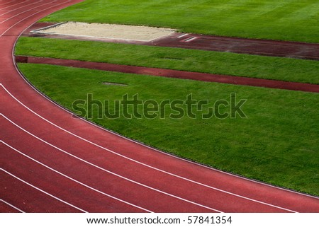 racetrack and long jump pit - stock photo