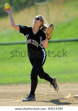 RACHEL, WV - APRIL 21: A North Marion HS (WV) softball player throws the ball in the infield during pregame drills prior to a game April 21, 2011 in Rachel, WV. - stock photo