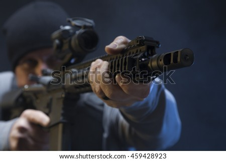 Rack focus of Undercover Law Enforcement Special Agent with weapon, aiming at a target. - stock photo
