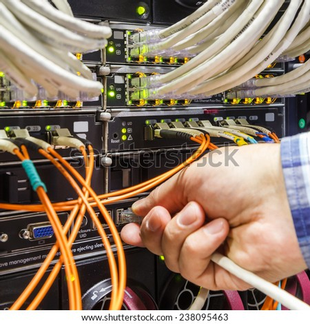 rack in the data center with working equipment with optical and and hand with connector - stock photo