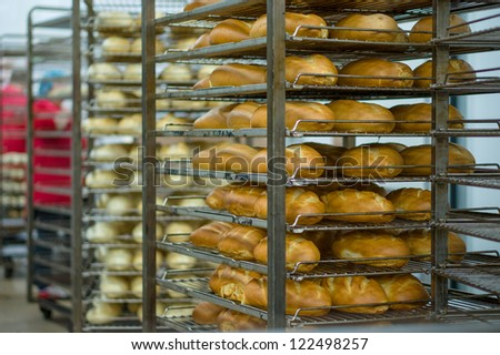 Rack trolley with baked bread and non baked bred in supermarket department - stock photo