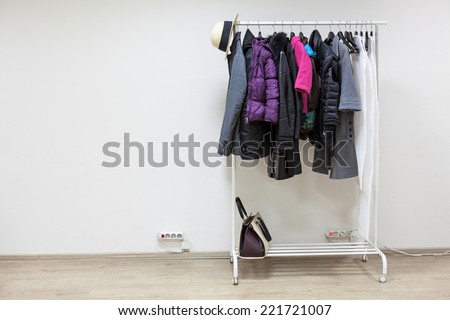 Rack with outerwear standing on the floor of white hallway room, copyspace - stock photo