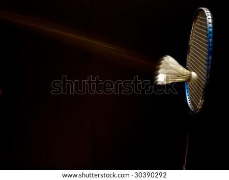 Racket and shuttlecock over black - stock photo