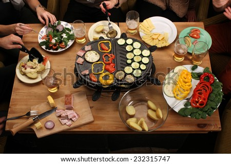 Raclette grill party - friends eating grilled vegetable, drinking beer on vintage wooden desk - stock photo