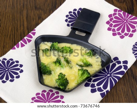 Raclette pan with cheese and broccoli on colorful napkin - stock photo