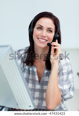 Radiant businesswoman with headset on working at a computer in a call-center - stock photo