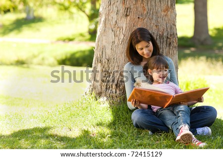 Radiant mother with her daughter looking at their album photo - stock photo