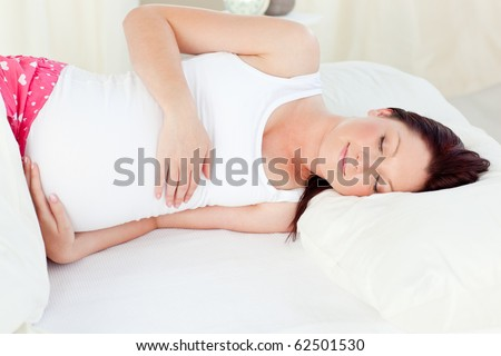 Radiant pregnant woman sleeping in her bed at home - stock photo