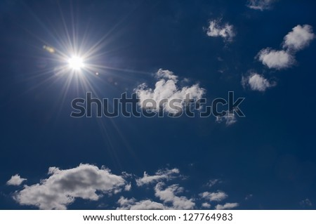 Radiant sun on blue sky with some clouds - stock photo