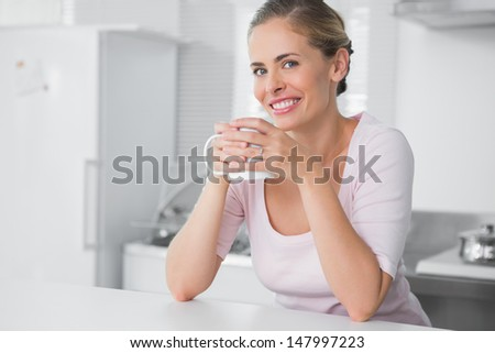 Radiant woman having coffee in her kitchen - stock photo